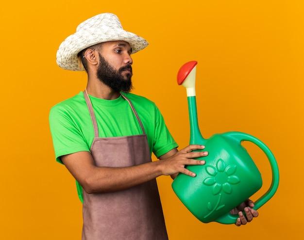 Denkende jonge tuinman afro-amerikaanse man met een tuinhoed die vasthoudt en kijkt naar een gieter geïsoleerd op een oranje muur