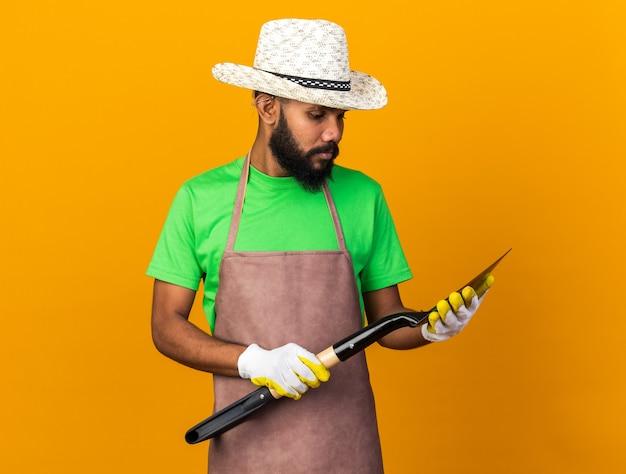 Denkende jonge tuinman afro-amerikaanse man met een tuinhoed en handschoenen die een schop vasthoudt en kijkt geïsoleerd op een oranje muur