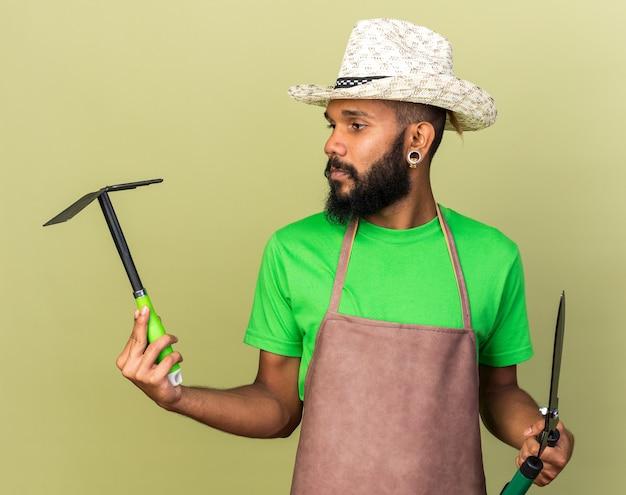 Denkende jonge tuinman afro-amerikaanse man met een tuinhoed met een tondeuse en een schoffelhark