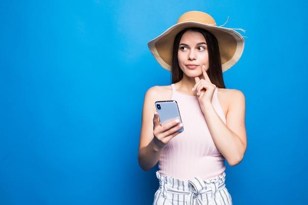 Denkende jonge vrouw in strohoed die mobiele telefoon met behulp van die over blauwe muur wordt geïsoleerd.