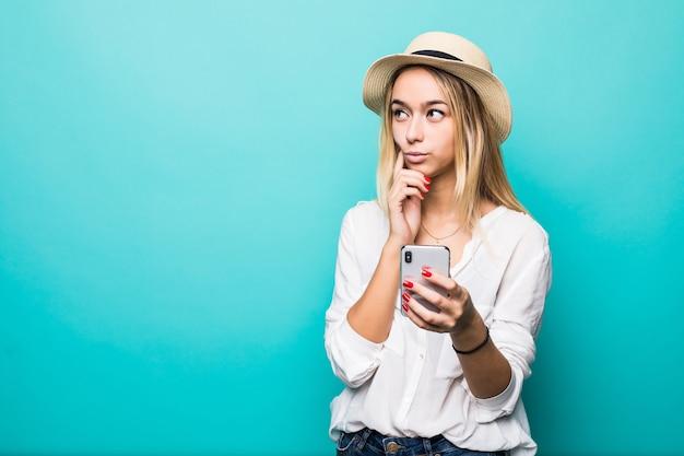 Denkende jonge vrouw in strohoed die mobiele telefoon met behulp van die over blauwe muur wordt geïsoleerd