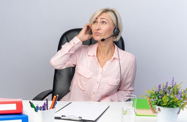 Denkende jonge vrouwelijke callcentermedewerker met een headset die aan tafel zit met kantoorhulpmiddelen geïsoleerd op een witte muur