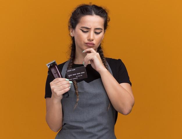 Denkende jonge vrouwelijke kapper in uniform vasthouden en kijken naar creditcard met tondeuses die de hand op de kin zetten die op de oranje muur is geïsoleerd