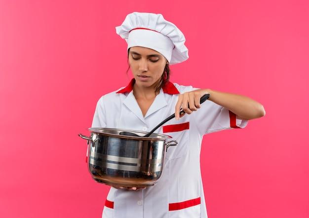 Denkende jonge vrouwelijke kok die chef-kok eenvormige holding draagt en steelpan met exemplaarruimte kijkt