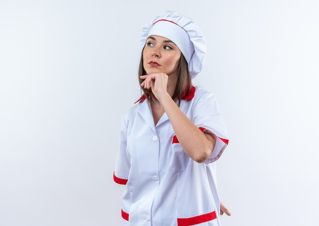Denkende jonge vrouwelijke kok die chef-kokuniform draagt, greep kin geïsoleerd op een witte muur