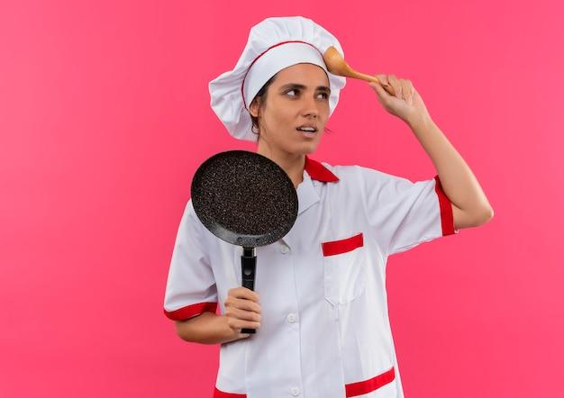 Denkende jonge vrouwelijke kok die de koekenpan van de chef-kok eenvormige holding draagt ?? die lepel op voorhoofd met exemplaarruimte zet