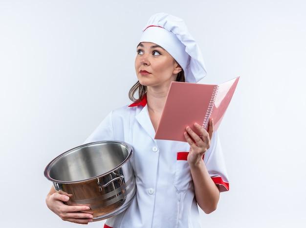 Denkende jonge vrouwelijke kok die een chef-kok uniform draagt en een steelpan vasthoudt met een notitieboekje dat op een witte achtergrond wordt geïsoleerd