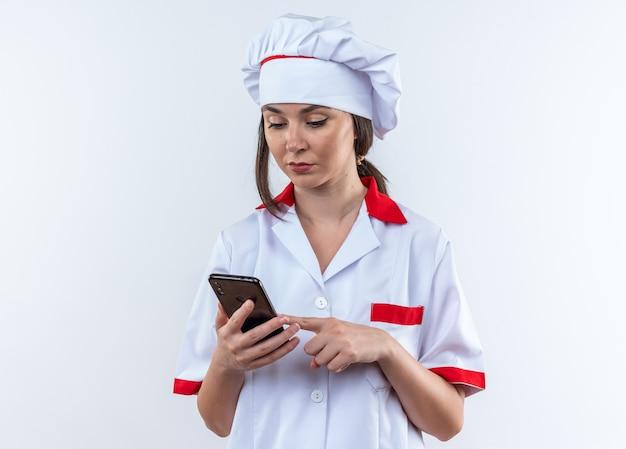 Denkende jonge vrouwelijke kok die een chef-kokuniform draagt en naar een telefoon kijkt die op een witte muur wordt geïsoleerd