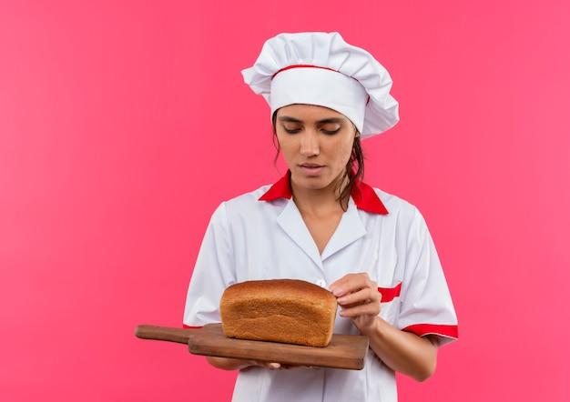 Denkende jonge vrouwelijke kok die eenvormige chef-kok draagt ?? en brood op scherpe raad met exemplaarruimte bekijkt