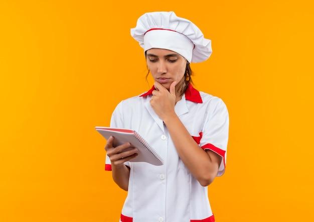 Denkende jonge vrouwelijke kok die eenvormige chef-kok draagt en notitieboekje bekijkt en hand onder kin met exemplaarruimte zet