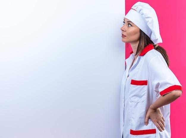 Denkende jonge vrouwelijke kok met uniform van de chef-kok staat in de buurt van een witte muur geïsoleerd op een roze achtergrond met kopieerruimte