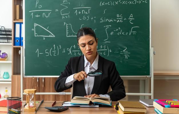 Denkende jonge vrouwelijke leraar zit aan tafel met schoolbenodigdheden leesboek met vergrootglas in de klas