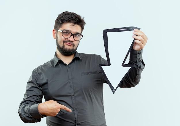 Denkende jonge zakenman die glazen draagt die richtingsteken en punten aan kant houden die op wit wordt geïsoleerd