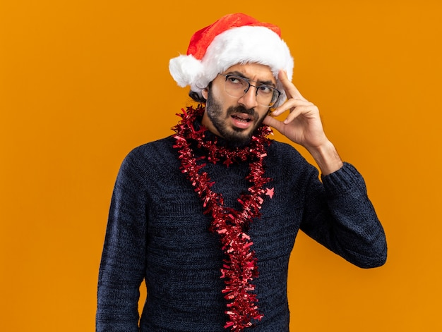 Denkende kijkende jonge knappe kerel met een kerstmuts met een guirlande op de nek en zet de hand op het hoofd geïsoleerd op een oranje muur