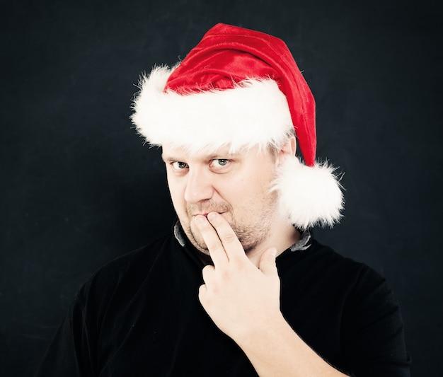 Denkende man met kerstmuts op donker