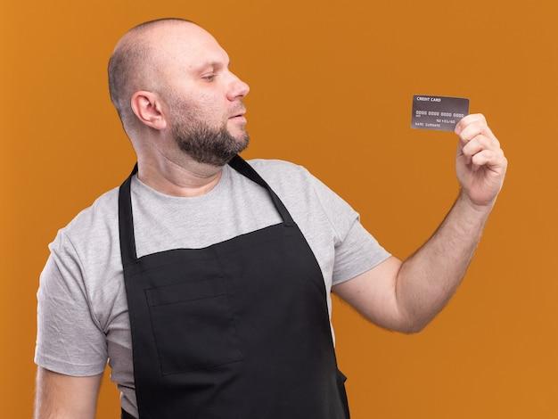 Denkende mannelijke kapper van middelbare leeftijd in uniform vasthouden en kijken naar creditcard geïsoleerd op oranje muur