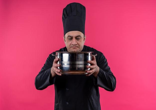 Denkende mannelijke kok van middelbare leeftijd in eenvormige chef-kok die steelpan in zijn hand met exemplaarruimte bekijkt