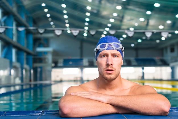 Denkende mannelijke zwemmer die fotograaf bekijkt