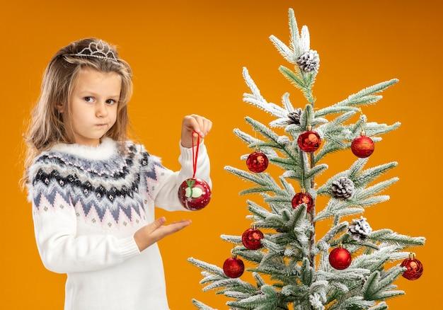 Denkende meisje dat zich dichtbij kerstboom bevindt die tiara met slinger op halsholding en punten op kerstmisbal houdt die op oranje achtergrond wordt geïsoleerd