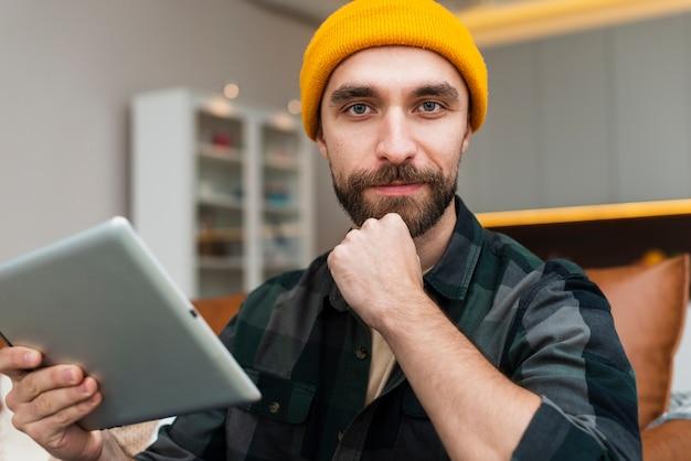 Denkende mens die een tablet houdt