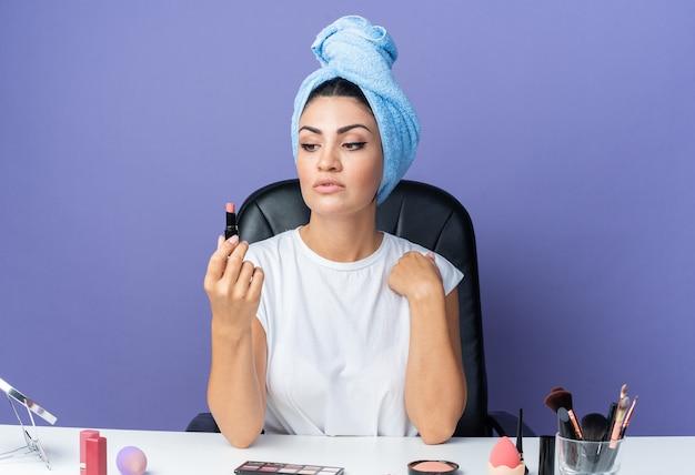 Denkende mooie vrouw zit aan tafel met make-uptools gewikkeld haar in handdoek vasthoudend en kijkend naar lippenstift