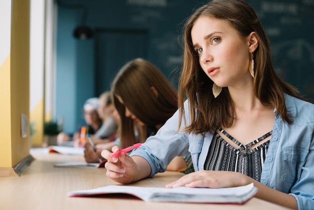 Denkende schoolmeisje kijken naar camera