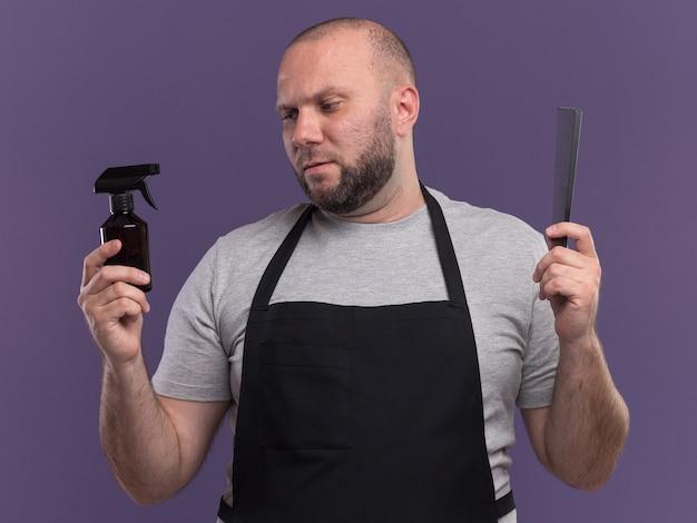 Denkende slavische mannelijke kapper van middelbare leeftijd in uniforme kam houden en op zoek naar spuitfles in zijn hand geïsoleerd op paarse muur