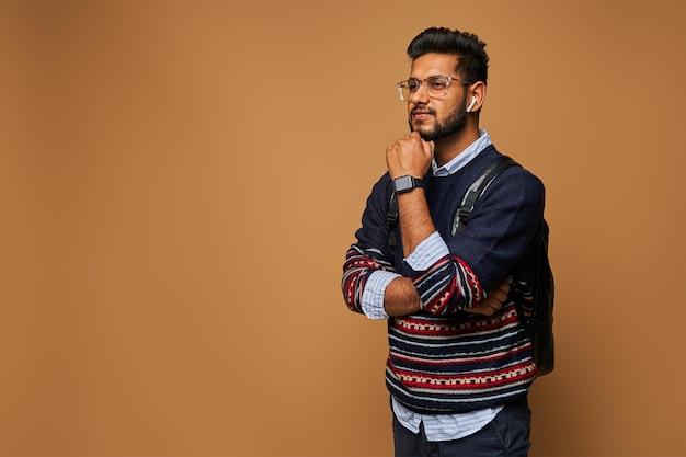 Denkende slimme indiase student met gekruiste armen die op de muur staat met kopieerruimte.