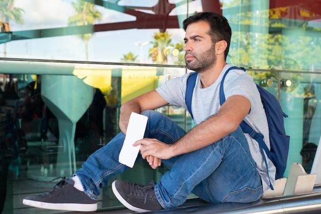 Denkende spaanse reiziger die kaartje houdt