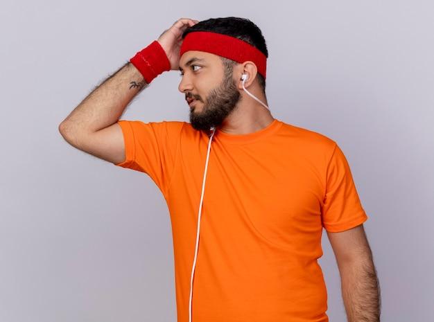 Denkende sportieve jongeman kijken kant dragen hoofdband en polsbandje met koptelefoon op schouder krabben hoofd geïsoleerd op een witte achtergrond