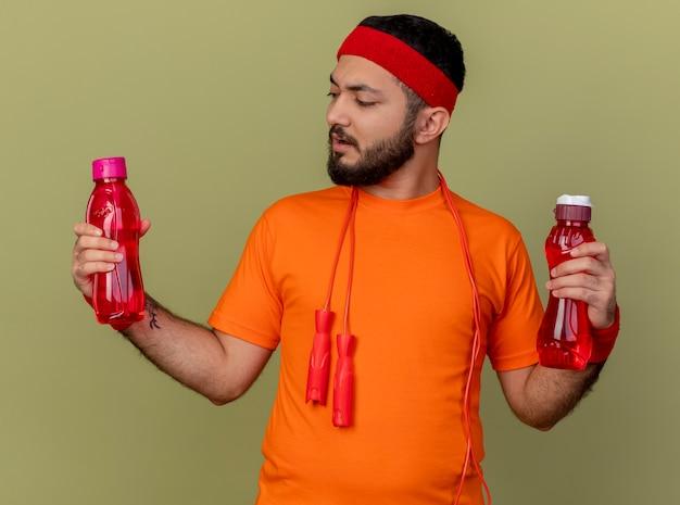 Denkende sportieve jongeman met hoofdband en polsbandje houden en kijken naar waterfles met springtouw op schouder geïsoleerd op olijfgroene achtergrond