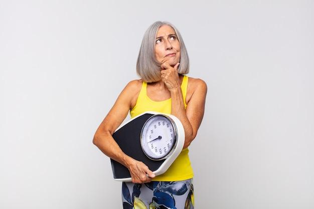 Denkende, twijfelachtige en verwarde vrouw van middelbare leeftijd, met verschillende opties, zich afvragend welke beslissing ze moest nemen. fitness concept