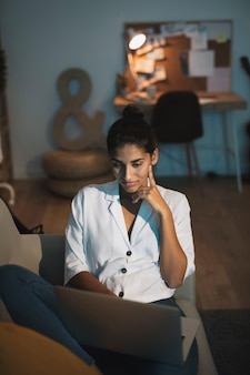 Denkende vrouw die aan laptop van huis werkt