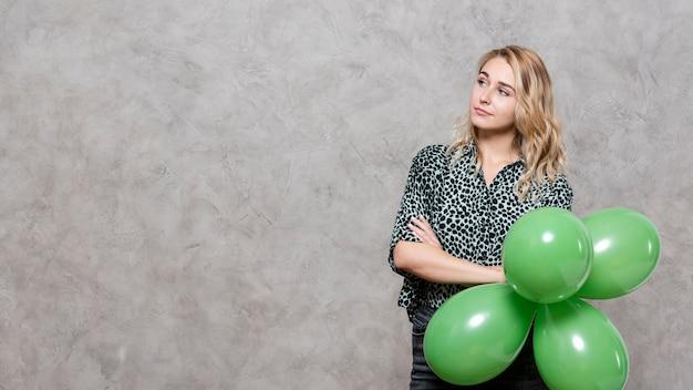 Denkende vrouw die een bos van ballons houdt