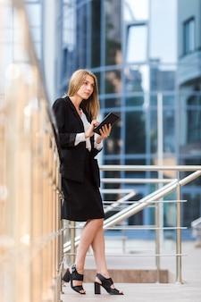 Denkende vrouw die een tablet houdt
