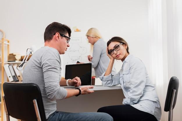 Denkende vrouw die met de mens op kantoor spreekt