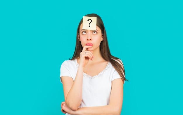 Denkende vrouw die met vraagteken omhoog kijkt. twijfelachtig meisje dat vragen aan zichzelf stelt. papieren notities met vraagtekens. verward vrouwelijk denken met vraagteken op kleverige nota op voorhoofd.
