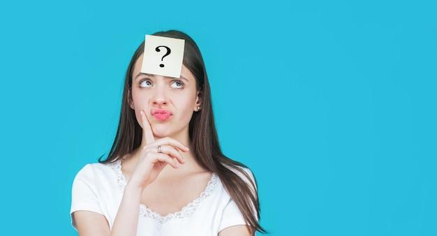 Denkende vrouw met vraagteken. twijfelachtig meisje stelt zichzelf vragen. aantekeningen op papier