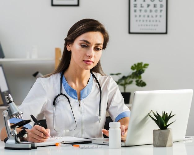 Denkende vrouwelijke arts die op laptop kijkt