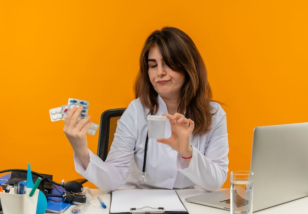Denkende vrouwelijke arts van middelbare leeftijd die medische mantel met stethoscoop draagt die aan bureau werkt op laptop met medische hulpmiddelen die leeg blikje met pillen op geïsoleerde oranje muur houden en bekijken