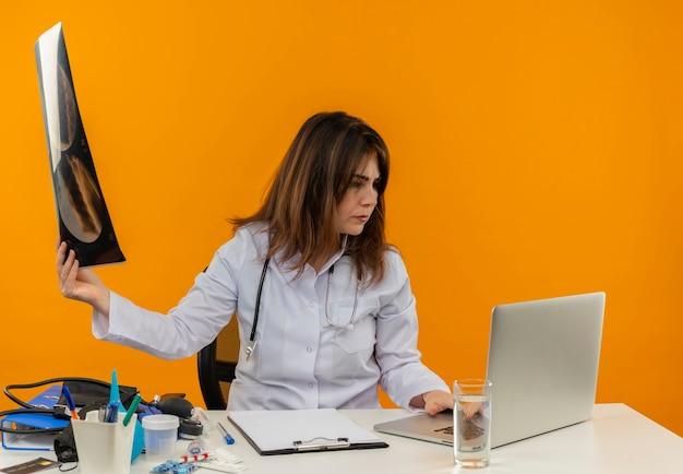 Denkende vrouwelijke arts van middelbare leeftijd die medische mantel met stethoscoop draagt die aan bureau zit werkt op laptop met medische hulpmiddelen die röntgenfoto houdt en laptop op geïsoleerde oranje muur bekijkt