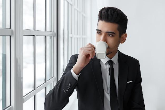 Denkende zakenman in pak zittend op de vensterbank en drinkt koffie.