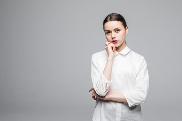 Denkende zakenvrouw die lacht en omhoog kijkt naar kopieerruimte. mooie jonge professional geïsoleerd op een witte muur.