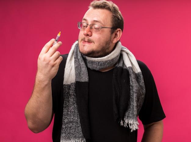 Denkende zieke man van middelbare leeftijd die een sjaal vasthoudt en naar een spuit kijkt