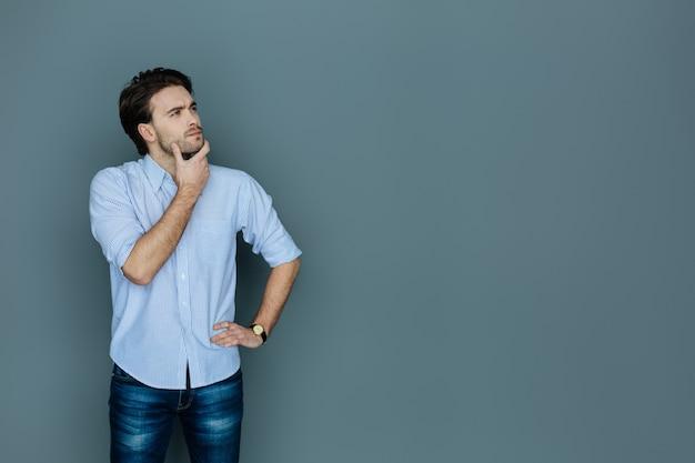 Denkproces. aardige knappe jonge man die tegen grote achtergrond staat en zijn kin vasthoudt terwijl hij nadenkt