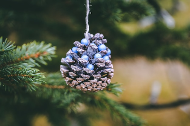 Denneappel met blauwe parels op kerstboom.