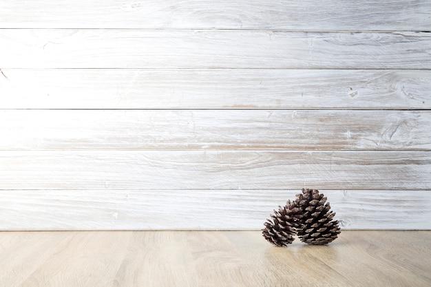 Denneappels met witte houten muur