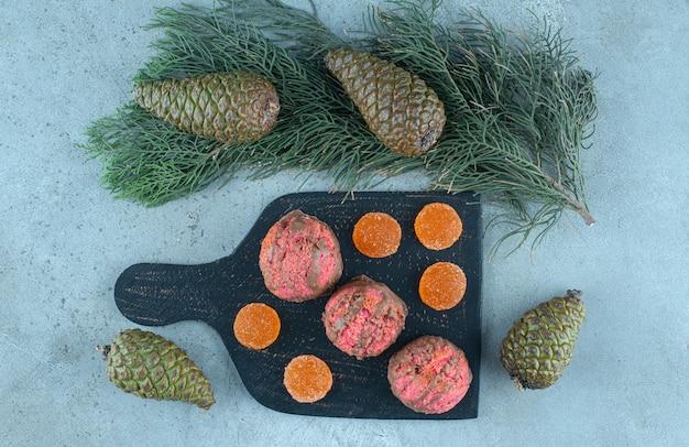 Denneappels rond een bord met desserts op marmer.