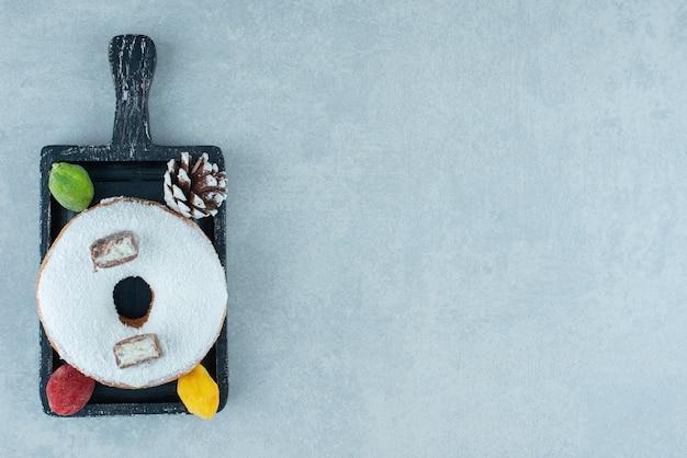 Dennenappel, marmelades en een donut op een zwart dienblad op marmer.