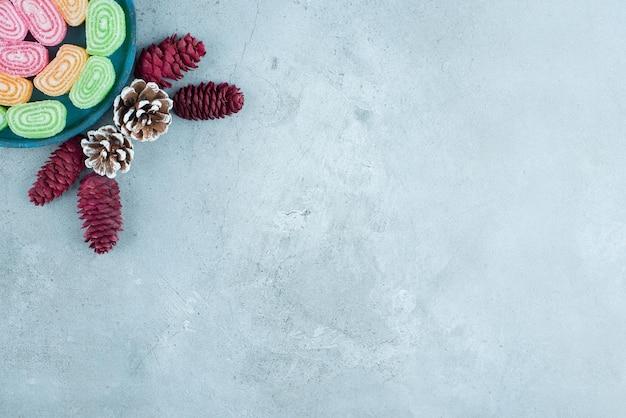 Dennenappelarrangement en een schaal met marmelades op marmer.